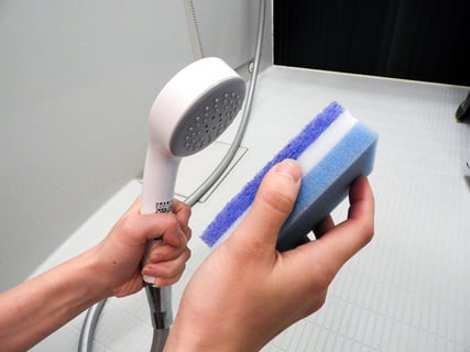 シャワーヘッドをスポンジでこする