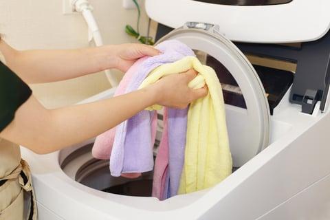 洗濯機に洋服を入れる
