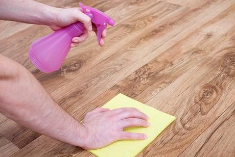 フローリングの床にスプレーを吹きかけ掃除する