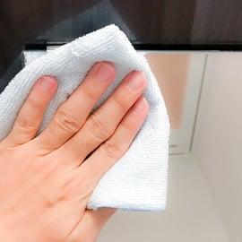 お風呂の鏡をタオルで拭く