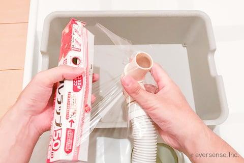 洗濯機の排水ホースにラップをかぶせる