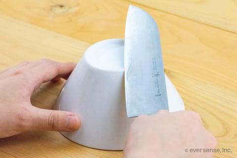 陶器の底で包丁を研ぐ