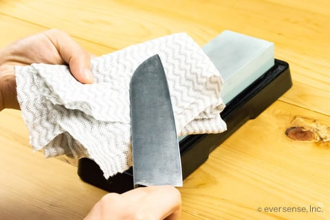 砥石で研いだ包丁を拭く