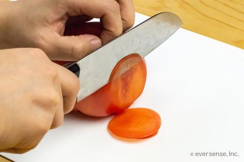 研いだ包丁でトマトを薄切りする